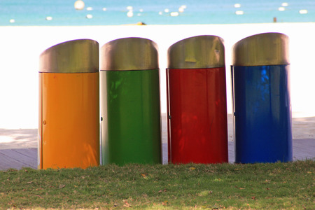 Row of four colored trash bins in yellow, green, red and blue on a beach with the sea in the background symbolizing recycling in public places and individual responsibility for throwing away rubbish