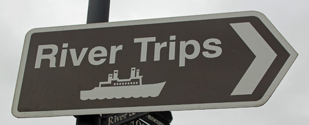 denoting: Brown tourist sign denoting River Trips symbolizing tourism, summer, vacations and holidays Stock Photo