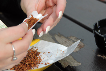 rolling up: Close-up of a ladies hands rolling up a cigarette symbolizing the dangers of smoking and the rise of using loose tobacco and roll-ups