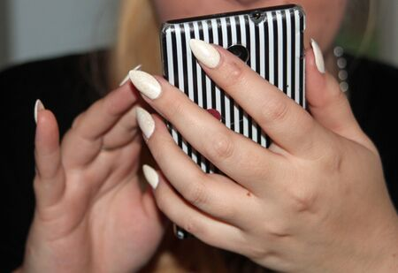 prevalent: Close up of a young ladys hands with manicured nails on a mobile phone symbolizing the use of mobiles and prevalent use of smartphones