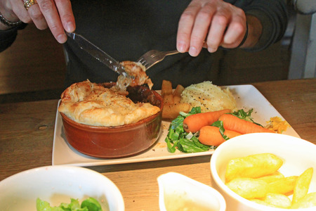 denoted: Pub food denoted by steak and kidney pie and chips with vegetables symbolizing pub food, rustic, hearty meals and homemade dinners Stock Photo