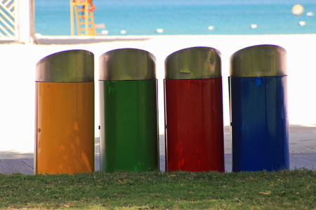 wastebasket: Row of four colored trash bins in yellow, green, red and blue on a beach with the sea in the background symbolizing recycling in public places and individual responsibility for throwing away rubbish