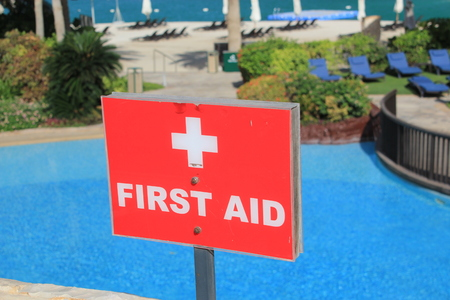 first aid sign: Close up of a First Aid sign with white text on a red background. Behind the First Aid sign is a turquoise swimming pool with sun loungers on the grass and the beach and sea in the distance.  The photo symbolizes accidents on vacations and the need for sa Stock Photo