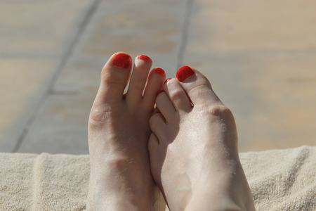 holiday destinations: Womans feet with pedicured nails on a sun lounger next to the pool or beach symbolizing vacations, holiday destinations and relaxation