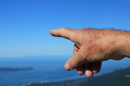 nonverbal communication: Mans hand pointing into the distance Stock Photo