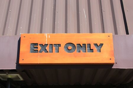 no way out: Wooden sign with black capital letters stating EXIT ONLY indicating the way out or exit