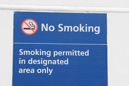 stating: Sign stating No Smoking - Smoking permitted in designated area only