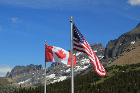 silver maple: American and Canadian flags, showing the full stars and stripes and maple leaf respectively, on silver flagpoles blowing in the wind against a backdrop of snow covered mountains and forest trees Stock Photo