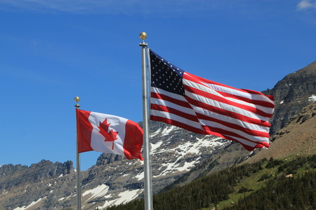 canadian flag american flag: American and Canadian flags, showing the full stars and stripes and maple leaf respectively, on silver flagpoles blowing in the wind against a backdrop of snow covered mountains and forest trees Stock Photo