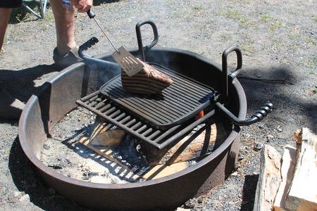 hombre cocinando: Hombre que cocina un gran pedazo de carne en una parrilla de barbacoa en un pozo de fuego simbolizando cocinar barbacoa, hombres haciendo la cocina y cocinar al aire libre durante el verano Foto de archivo