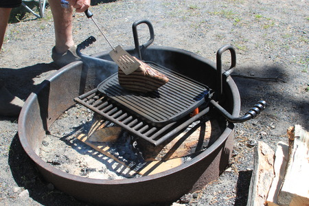 al fresco: Man cooking a large piece of steak on a BBQ grill over a fire pit symbolizing BBQ cooking, men doing the cooking and cooking outdoors during the summer Stock Photo
