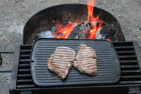 alfresco: Large flame grilled steaks on the BBQ.  The BBQ grill is over a fire showing the red flames, wood and charcoal Stock Photo