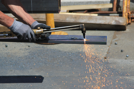 Man wearing protective gloves welding a metal sheet with sparks emitting from the oxy acetylene cutting torch Stock Photo
