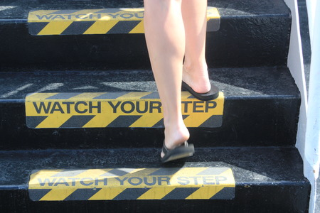 trip hazard sign: Person walking up stairs with yellow and black warning sign on each step stating Watch your Step signifying a potential trip hazard, steep stairs and care to be taken when going up or down stairs