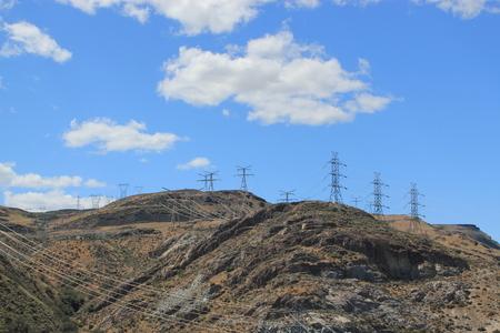 torres el�ctricas: Las torres de electricidad y cables de energ�a se extiende a trav�s del campo Foto de archivo