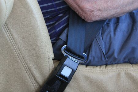 car lock: Senior man in a car wearing a seat belt showing a close up of seat belt locked as he is driving symbolizing car safety Stock Photo