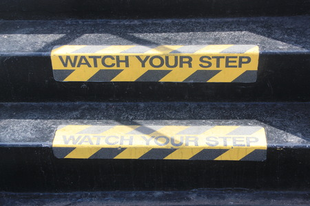 trip hazard sign: Yellow and black warning sign on stairs stating Watch your Step signifying a potential trip hazard, steep stairs and care to be taken when going up or down stairs