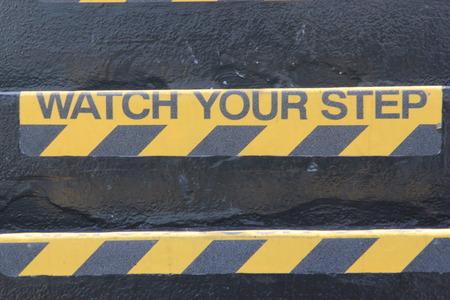 """bajando escaleras: Amarillo y negro se�al de advertencia en las escaleras que indican """"Watch Your Step"""" significando un peligro potencial viaje, escaleras empinadas y cuidados que deben tomarse al subir o bajar escaleras"""