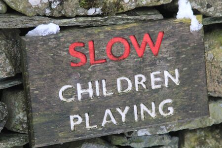 stating: Wooden sign on a dry stone wall stating SLOW CHILDREN PLAYING in red and white lettering indicating that children are playing in the area and traffic should go slowly