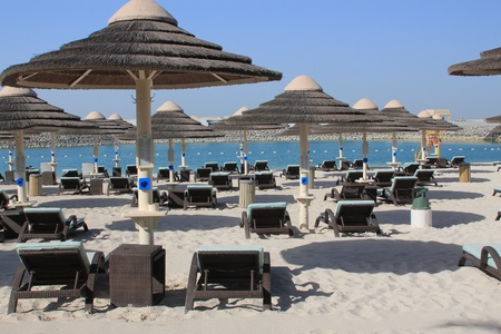Sun loungers and parasols on a white sand beach with blue sea symbolising luxury resorts, holiday and summer Standard-Bild