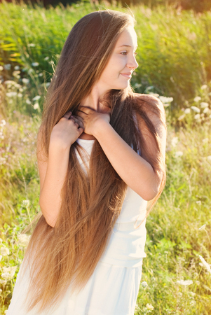 Beautiful Girl with very long Hair at the Meadow in Countryside on Sunshine. Healthy lifestyle