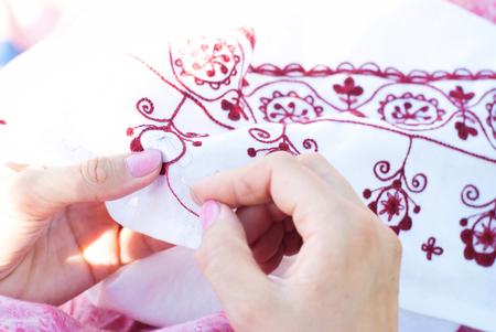 needlecraft: Woman Embroiders floral ornament on linen - Embroidery, handswork, needlecraft