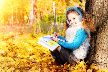 Beautiful Girl with Red Curly Hair Drawing Picture in the Autumn Park - Sunny Day - Autumn Fall Stock Photo