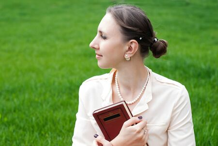 happieness: Romantic Portrait of Young Beautiful Woman in the Park with Book