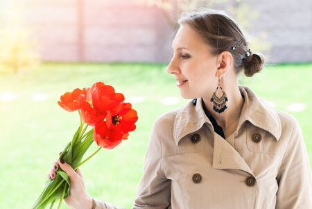 happieness: Romantic Portrait of Young Beautiful Woman in the Park with Red Tulips - Beauty and Fashion Concept