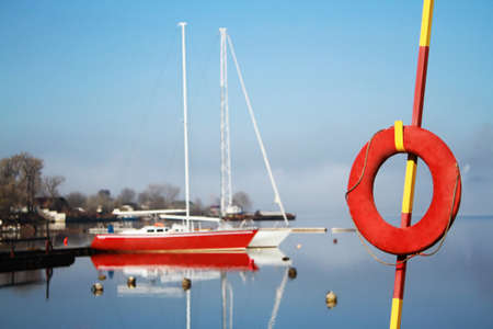 Red lifebuoy on a background of two yachts
