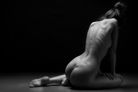 Hermoso cuerpo de mujer joven sobre fondo oscuro