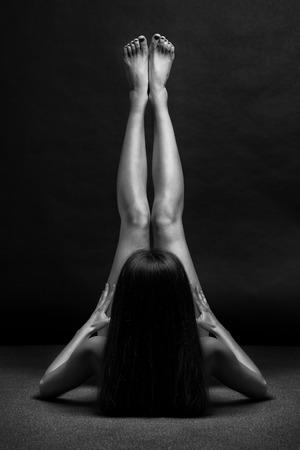 femme se deshabille: Beau corps de jeune femme sur fond sombre