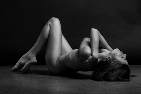 nude woman sitting: Beautiful body of young woman over dark background