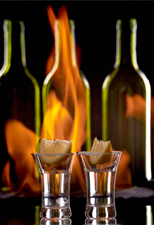 Tequila shot on flaming background