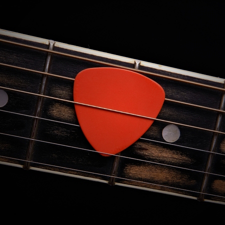 Orange guitar pick on the fingerboard Stock Photo - 22345138