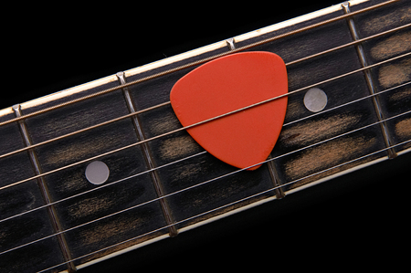 Orange guitar pick on the fingerboard Stock Photo - 22345139