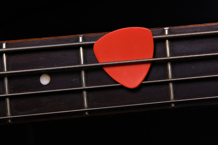 Orange guitar pick on the fingerboard photo