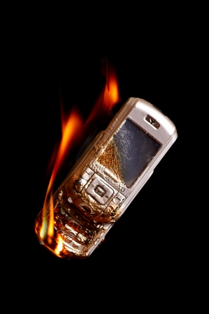 Burning cell phone on black background