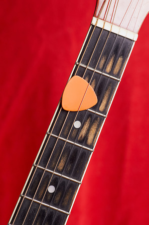 Orange guitar pick on the fingerboard Stock Photo - 22345228