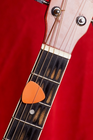 Orange guitar pick on the fingerboard Stock Photo - 22345229