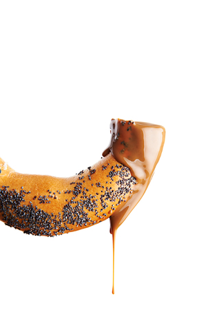 Bagel with poppy seeds and chocolate syrup isolated on white photo