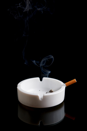 Cigarette in an ashtray on a black background photo