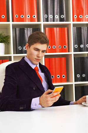 electronic organizer: Young businessman writing sms