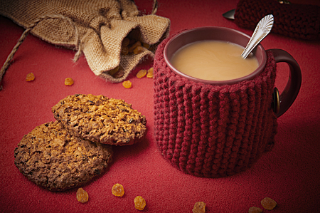 Knitted woolen mug with cookies photo