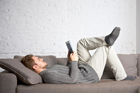 Young man using tablet on sofa at home Stock Photo