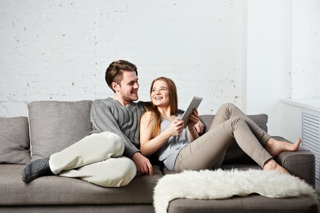 couple on couch: Romantic relaxed young couple using tablet computer on couch