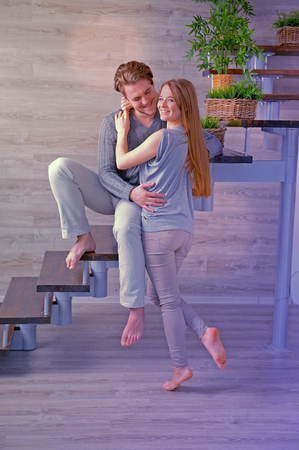 Young couple hugging while sitting on stairway in living room - instagram effect Stock Photo