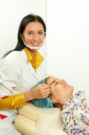 Smiling master with beautiful client. Brows coloring process. Beauty industry.