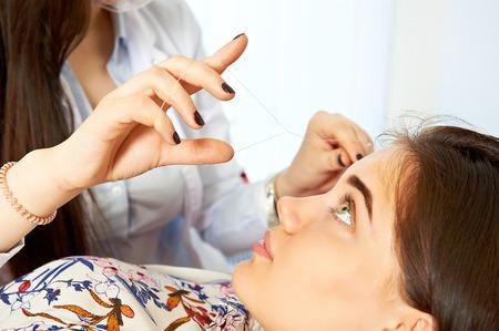 Stylist making eyebrow thread correction on face of beautiful girl
