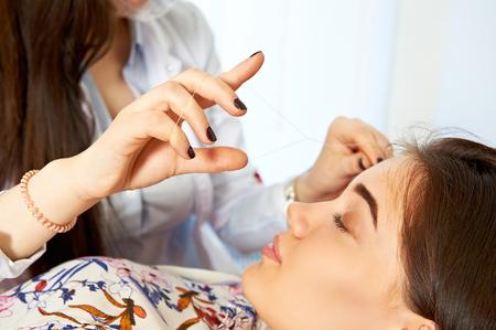 Stylist making wenkbrauw draad correctie op het gezicht van het mooie meisje Stockfoto